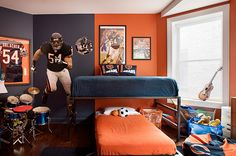 Navy blue & orange Bears themed boy's bedroom design with blue & orange walls paint color, twin beds, orange & blue bedding, drum set and Chicago Bears collectibles.