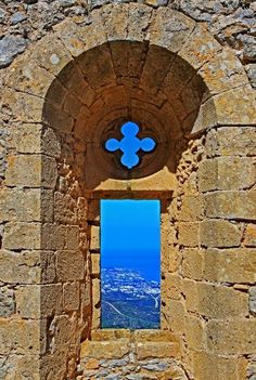 View through a window of the ruins of Saint Hilarion Castle (built 900's), overlooking the city of Girne, Cyprus.