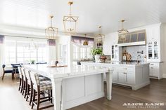 A cook's kitchen features a white beadboard ceiling dotted with four Darlana 4 Light Lanterns illuminating two kitchen islands topped with white marble with one island designated for prep work and the other island designated for a dining table lined with gray check counter stools. A steel kitchen hood is accented with brass trim and stands over a marble cooktop backsplash lined with a swing arm pot filler and a stainless steel stove with dual ovens. A farmhouse sink fitted with aged…