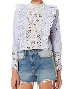 """Eyelet Ruffle Crop Blouse. A mix of eyelet and ruffles on a striped background makes for the perfect feminine piece. Button back closures. Flared cuffs at long sleeves. In blue.  Fabric: 100% cotton. Model Measurements: Height 5'10 1/2; Waist 24""""; Bust 31"""" wearing size 2. Length from shoulder to hem: 19"""" (Sea)"""