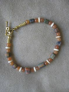 7″ African striped Sand-cast beads. $10.00 Amber glass rounds. Bone heishi.
