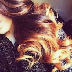 Fiery ombre a reddish dark brown to a golden blonde on the ends and thick curls.