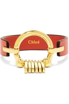 Polished hardware is a Chloé signature. This orange leather bracelet is accented with a gleaming gold-tone brass ring with tassel details. We think it contrasts perfectly with a breezy blouse or dress.