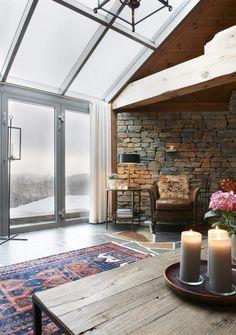 HØYT UNDER TAKET: Vinduene i taket i stuen på denne fjellhytta gir fri sikt rett opp til himmelen. Bruk av stein og tre gir en beskyttende følelse. Bordet, stolene og lampene fant eierne på en reise i USA.
