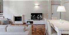 I progettisti di Studiòvo firmano la ristrutturazione di un appartamento di 120 mq con camera da letto in mansarda. Interessante, nel living, il trattamento delle pareti in un grigio chiaro fino a un bordino a stucco bianco che stacca visivamente rispetto al soffitto in legno. Sobrio il camino fornito da Borelli Marmi, più marcato invece il disegno del parquet. Il mobile porta-tv è di Citti, abitare in legno.