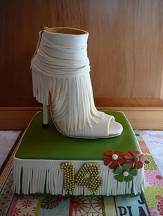 I had a request for a Gucci fringed shoe. It was a hard one, difficult to do, I think I will not make it twice!!! The shoe is made out of fondant and all edible, there is only a little stick on the heel. You can see the picture of the real shoe beside the fondant shoe. I used the template I already posted here on CC and changed it for the top part. It was not the optimal pattern, the fringed part saved me! The cake is chocolate with white chocolate ganache covered with fondant. The 14 years…