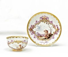Tea Bowl and Saucer with Landscape Scenes.   Meissen. Circa 1740.     Porcelain, enriched in colours and in gilt. A narrow, lace border lines the edges. Both tea bowl and saucer with oval gold cartouches with dark contours and purple feathers.