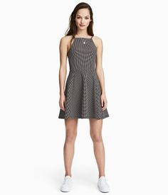 Black/dotted. Short dress in textured jersey with narrow shoulder straps, seam at waist, and circle skirt. Lower-cut back neckline and horizontal strap