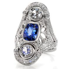 This vintage inspired wide ring design features a 1.00 carat royal blue sapphire. The vertical design also features two large full bezel set diamonds. The ornate pattern is decorated with pierced elements that are embellished in micro pavé set diamonds. This design is truly a statement piece.