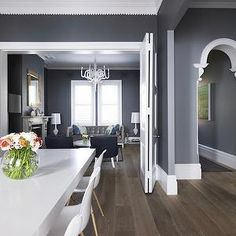 grey dining room Eames dowel leg chairs white chandeliers white moulding
