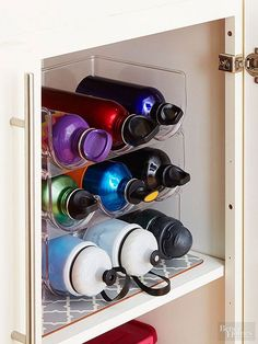 Rethink a wine rack's purpose, and you'll come up with a multitude of novel ways to put it to good use. In this kitchen cabinet, a tabletop wine bottle rack now holds waterbottles behind closed doors in tidy grab-and-go rows./