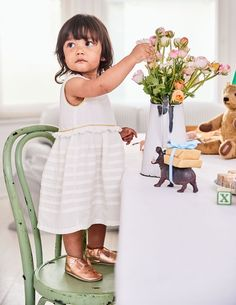 This pretty dress is perfect for bringing your baby to glittering occasions, thanks to a touch of sparkle in the trim. It's all about the details, from the layers of pintuck pleats to the delicate broderie trim. It comes with a matching pair of knickers, too.