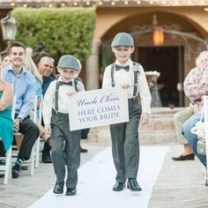"Two adorable ring bearers holding ""Here Comes Your Bride"" sign, grey bow ties, suspenders, and fedoras 
