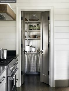 Planked walls in a kitchen. A great DIY woodwork idea. I also love the old-fashioned pantry with skirted shelving.