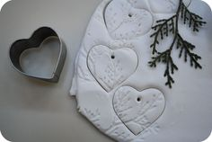 Use sculpy clay or bakers clay.  Imprint, cut out, paint if you want to, or not, string with twine.