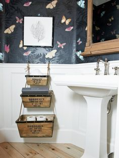 "When faced with a tight bathroom, designers have to get creative when planning storage. ""This was a small space with little room to spare for storage,"" says designer Kari Arendsen. ""I found these cute storage boxes and hung them from the wall to save space and keep floor space clear. Also the choice of a high contrast application on the walls is helpful to make a space feel larger than it really is."""