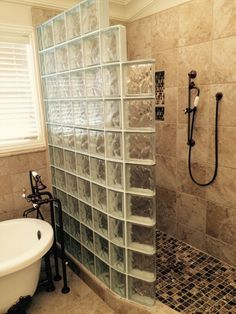 Curved glass block shower with a freestanding tub in California