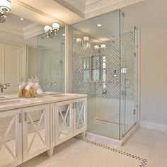 bathrooms - elegant baths, elegant bathrooms, sophisticated baths, sophisticated bathrooms, tray ceiling, dentil crown molding, double sink vanity, double washstand, mirrored sink vanity, mirrored double vanity, mirrored double washstand, double vanity with mirrored doors, marble countertops, vanity mirror, mosaic marble floor, bathroom tray ceiling, tray ceiling bathroom, corner shower, seamless glass shower, geometric shower tiles, geometric shower surround, white and gray shower tiles,