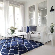 Raikas sininen väri matossa ja tyynyillä tuo kivaa energiaa olohuoneeseen.