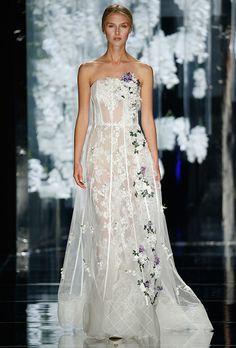 Brides.com: YolanCris - Spring 2016                          Strapless sheer A-line wedding dress with 3D floral embellishments and corset detail, YolanCris                                                                                  Photo: Courtesy of YolanCris