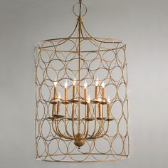 "Circle Cage Candles Chandelier  This large lantern style chandelier features a sleek shade of golden circles around a 2 tier cluster of candle lights for a striking statement in a two story foyer or vaulted ceiling room. 12-40watt max candelabra bulbs. Includes 44"" of matching chain with 5"" round canopy.  (37""Hx23""W)"
