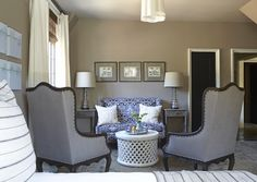 Gorgeous bedroom sitting area with taupe walls paint color, Barbara Barry Simple Scallop Pendant, blue wingback settee, white Bamileke cocktail table, gray linen wingback accent chairs, gray washed end tables and blue & gray rug.