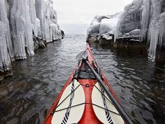 Kayaking past walls of ice formations while in a rock slot on Lake Superior. Grand Marais, MN