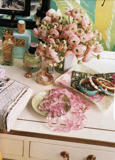 All the feminine necessities: pink flowers, bangles, perfume and a gold watch.