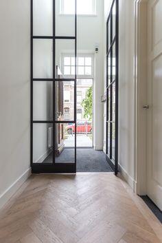 Entree met vide, waardoor er optimaal zonlicht in zowel de hal als boven op de overloop binnen komt. Fraaie combinatie van eikenhout, hoge glazen stalen taatsdeuren, strak stucwerk met een klassieke voordeur.