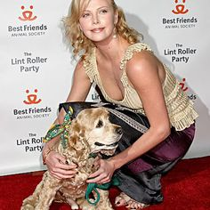 Charlize Theron, an Oscar winner, holds one of her cocker spaniels at a Hollywood party to benefit homeless animals.