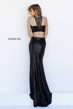 Raise the stakes in the slinky, sensually sequined, black Sherri Hill 32297 full-length dress. This stunning two-piece gown creates a fabulous fit and flare silhouette. The halter neck cropped top showcases a tapered center back illusion strap, replicating the sexy illusion inset on the center back waist of the skirt. The long skirt hugs the hips, fanning into a flared hemline with slight train. The all over sequin look is spectacular.