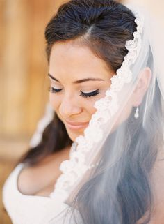If you are wearing a veil, make sure to have your photographer snap this romantic shot of you looking down from behind your veil — plus, it's a great way to see your eye shadow.  Photo by Esther Sun Photography via Jessica Burke