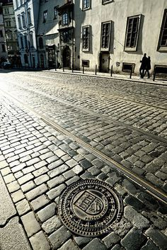 Two people walking along the cobbled side-streets of Prague in the Czech Republic