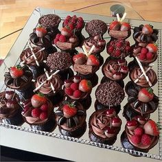 Assorted cupcakes decorated with mini oreo biscuits, toffee bonbons, chocolate sticks and strawberries dipped in chocolate.