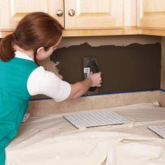 2. Tape ladle thin-set mortar onto the wall and carefully work it with a notched towel to make smooth, even ridges.
