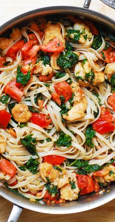 Shrimp pasta with fresh tomatoes and spinach in a garlic butter sauce.