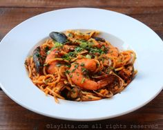 Receta para preparar pastas con mariscos en salsa roja o tallarines con mariscos con un toque latino. Esta receta se prepara con una mezcla de camarones, mejillones, conchas, calamar, pescado, y más.