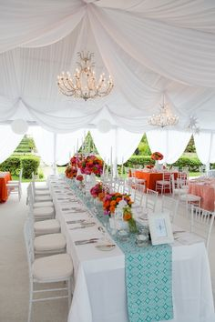 A reception underneath a draped canopy on white plush carpet creates a welcoming retreat for your guests.