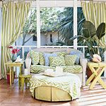 white wicker loveseat with pale green and blue pillows and cushions