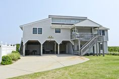 """As the sign says when you walk in the front door, """"Welcome to Ben and Judy's beach house"""". Your state of mind will be refreshed after you have stayed in this fabulous oceanfront vacation home. Offering stunning ocean views this home is located in the prestigious Village of Duck, NC. and you will need for nothing more!Nestled on the renowned wide, clean beaches of Duck, you are sure to find this coastal five-bedroom home to be what you have been waiting for. The gorgeous views of the ocean…"""