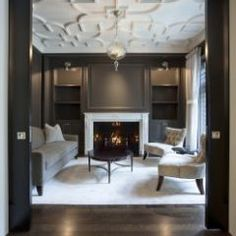 Textured ceiling. Dark walls lightened by furniture and cabinet sconces.