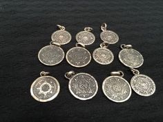 LARGE GROUPING OF STERLING SILVER AZTEC CALENDAR STONE PENDANTS AND CHARMS WEIGHING 32 GRAMS TOTAL. MOST ARE ABOUT .75 INCHES IN DIAMETER. C