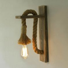 Greek based TassoStudio hand created a wall lamp made out of reclaimed weathered wood and discarded rope. The design shows a great contrast. #Lamps #Lamps&LightingIdeas #WoodenLamp
