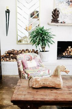 An eclectic living space with indoor plant, fireplace with stacked wood, and thrift-store finds