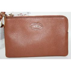 """Coach  Embossed Small L-Zip Wristlet Coach  Embossed Small L-Zip Wristlet  Color: Saddle/Brown Style: 52553 Retail: $65.00  Crafted in soft pebbled leather in an array of striking colors, this luxe little wristlet keeps lipstick, phone, cash and keys neatly organized. Wear the iconic style strapped to the wrist or clipped inside of a larger bag.  Two credit card pockets Zip closure, fabric lining Strap with clip to form a wrist strap or attach to the inside of a bag 6 1/4 (L) x 4"""" (H) Coach…"""