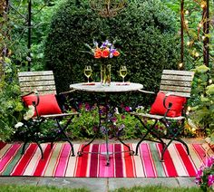 An outdoor rug can cover a worn or unremarkable surface while also adding warmth, color, and an indoor touch. This rug echoes the vibrant hues of the annual blooms nearby. Similar to shown: Koko Company Melange 6-by-8-foot Indoor/Outdoor Floor Mat in Tutti Frutti Red Mix, about $100; Hayneedle.com