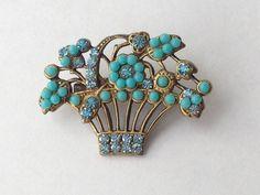 Turquoise glass beads w/ rhinestones set on gold toned metal flower basket pin.