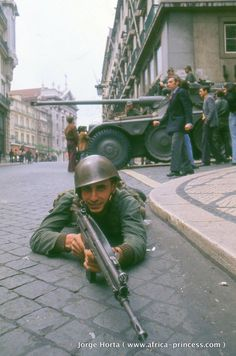 """1974 Carnation Revolution - Portuguese Army soldiers and armored cars of the left-wing revolutionary Armed Forces Movement (Movimento das Forças Armadas) mobilize on the streets of Lisbon in a coup d'etat against the Fascist """"Estado Novo"""" regime. History Of Portugal, World Conflicts, April 25, Guinea Bissau, World History, Military History, France, Colorful Pictures, Lisbon"""