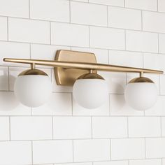 """Linear Globe Bath Light - 3 Light Simple modernity defines this bath light, which features three globe lights mounted on a tapered bar. Available in Natural Brass and Polished Chrome finishes. Certified for Damp location. 3x50 watt G9 base bulb max. (7.75""""Hx24.50""""Wx6""""E)"""