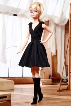 """Classic Black Dress Barbie® Doll The Barbie CollectionThe little black dress is a staple in any sophisticated wardrobe. Barbie® doll wears this classic with an air of modern chic, featuring a dramatic deep """"V"""" neckline and feminine bows at the shoulders. Tall boots and a signature ponytail complete the oh-so-fabulous look. For the first time ever, the 2016 BFMC series features a posable Silkstone® body, for endless posing possibilities."""